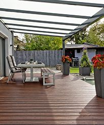 A covered outdoor patio built with Trex Transcend decking with a patio table