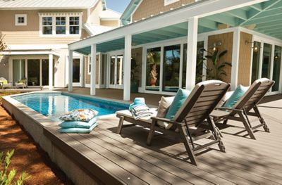 Trex Transcend®-Terrassendielen in Gravel Path-Grau, gerahmt von Trex-Terrassenmöbeln auf einer Poolterrasse wie im 2013HGTV Smart Home gezeigt.